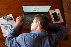 睡觉在膝上型计算机键盘的疲乏的被用尽的商人顶视图在工作场所 英俊的劳累过度的自由职业者人 免版税库存照片