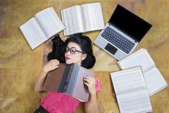 睡觉在膝上型计算机附近的女学生 免版税图库摄影