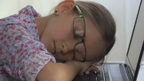睡觉在膝上型计算机,笔记本,书桌的近视的女孩的镜片孩子 免版税库存图片