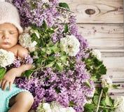 睡觉在花的逗人喜爱的孩子 图库摄影