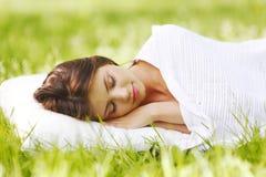 睡觉在草的妇女 免版税库存图片