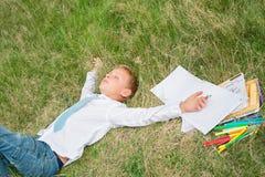 睡觉在草的男小学生 库存图片