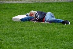 睡觉在草的资深无家可归的人 免版税库存照片