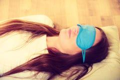 睡觉在蓝眼睛睡眠面具的深色的妇女 库存照片