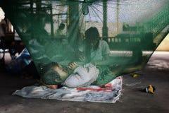 睡觉在蚊帐的可爱的逗人喜爱的小孩,当她的工作在背景中时的母亲 库存照片