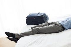 睡觉在行李旁边的商人的低部分在旅馆客房 免版税库存图片