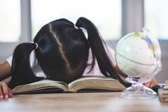 睡觉在被打开的书的疲乏的亚裔儿童女孩在教室 免版税库存照片