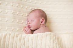 睡觉在被编织的毯子下的微小的新出生的婴孩 图库摄影