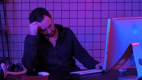 睡觉在计算机附近的疲乏的黑客,当计算机处理时 库存图片