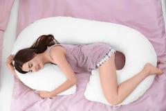睡觉在身体枕头的年轻美丽的妇女 图库摄影