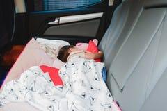 睡觉在车里面的孩子没有一个与她,危险把您的孩子留在汽车 库存照片