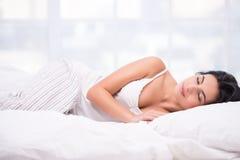睡觉在镶边睡衣的少妇 免版税库存照片