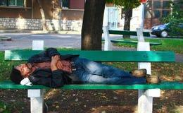 睡觉在长凳的疲乏的无家可归的人 免版税图库摄影