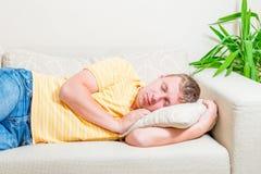 睡觉在长沙发的一个人的画象 免版税库存照片