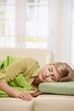 睡觉在长沙发的白肤金发的妇女 免版税库存图片