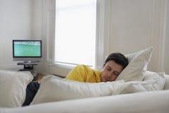 睡觉在长沙发的年轻人 库存照片