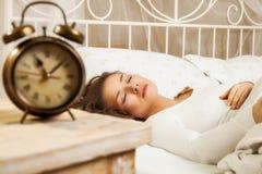 睡觉在闹钟旁边的床上的妇女 库存图片