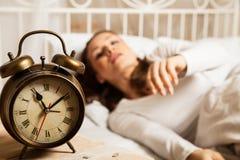 睡觉在闹钟旁边的床上的妇女 库存照片
