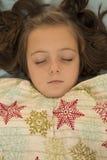 睡觉在雪花毯子下的可爱的女孩 库存照片
