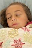 睡觉在雪花毯子下的美丽的女孩 免版税图库摄影