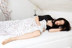 睡觉在黑晨衣的床上的年轻人和美女 库存图片