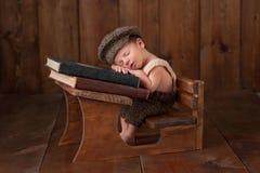 睡觉在他的学校书桌的新出生的男婴 库存图片
