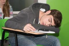 睡觉在类的少年 免版税库存图片