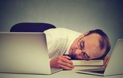 睡觉在他的有膝上型计算机的书桌的商人,疲乏的中部变老了人雇员 免版税库存照片