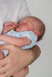 睡觉在他的父亲的胳膊的婴孩 免版税图库摄影