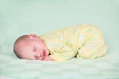 睡觉在绿色毯子的甜新出生的婴孩 库存图片