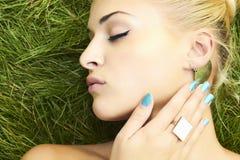 睡觉在绿草的美丽的白肤金发的女孩。秀丽妇女 免版税库存照片