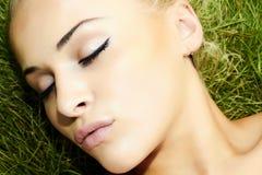 睡觉在绿草的美丽的白肤金发的女孩。秀丽妇女 图库摄影