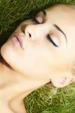 睡觉在绿草的美丽的白肤金发的女孩。秀丽妇女 库存图片