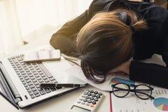 睡觉在workpla的膝上型计算机的劳累过度和疲乏的女实业家 免版税库存图片