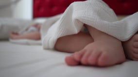 睡觉婴孩关闭的腿在一条白色毯子,慢动作下 影视素材