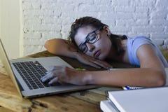 睡觉年轻美丽和疲乏的学生的女孩采取说谎在家庭便携式计算机书桌上的休息用尽了并且浪费了在附近花费 免版税库存图片