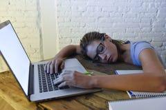 睡觉年轻美丽和疲乏的学生的女孩采取说谎在家庭便携式计算机书桌上的休息用尽了并且浪费了在附近花费 库存照片