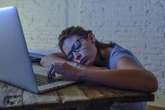 睡觉年轻美丽和疲乏的学生的女孩采取说谎在家庭便携式计算机书桌上的休息用尽了并且浪费了在附近花费 免版税库存照片