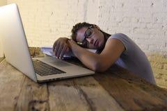 睡觉年轻美丽和疲乏的学生的女孩采取说谎在家庭便携式计算机书桌上的休息用尽了并且浪费了在附近花费 图库摄影
