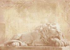 睡觉狮子雕象在难看的东西背景的与在石头的被雕刻的建筑细节作为在门面大厦的装饰 免版税库存照片