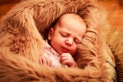 睡觉用小手的新出生的婴孩在面颊附近 免版税库存照片