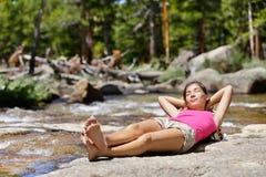睡觉由河的松弛妇女远足者本质上 免版税库存照片