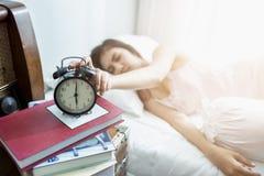 睡觉的亚洲妇女和闹钟醒 免版税库存照片