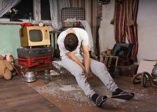 睡觉的人坐笼子在破烂物室 免版税库存图片