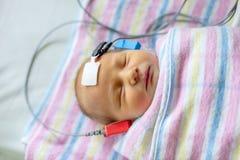 睡觉的听觉测验新出生在医院 免版税库存照片