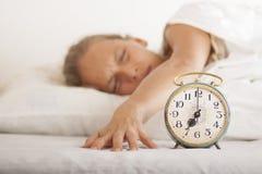 年轻睡觉的妇女和闹钟在床上 免版税库存照片