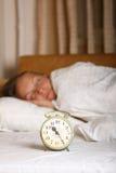 年轻睡觉的妇女和闹钟在床上 库存图片