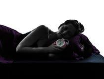 睡觉的妇女在床上拥抱闹钟剪影 免版税库存照片