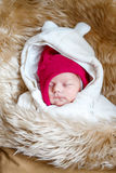 睡觉的新出生的婴孩画象在温暖的冬天穿衣 库存图片