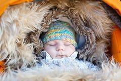 睡觉的新出生的婴孩画象在温暖的冬天穿衣 库存照片